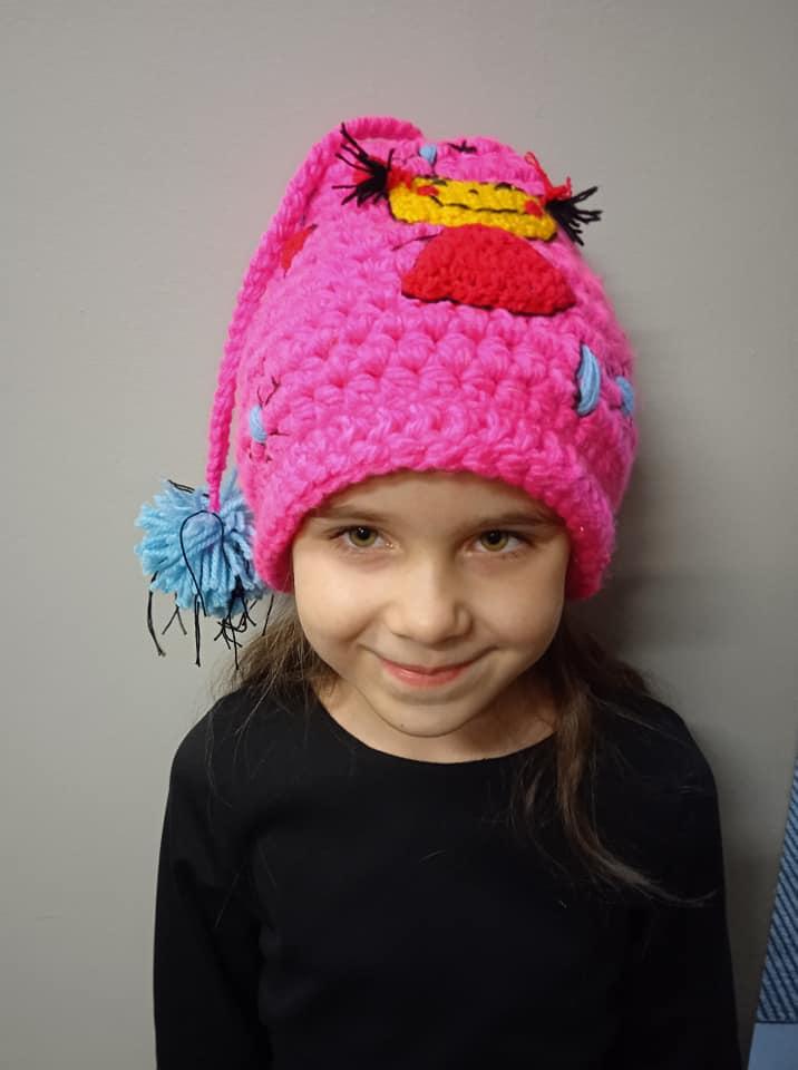 uśmiechnięta dziewczyna w różowej czapce