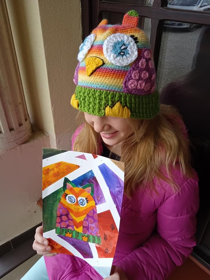 dziewczynka w czapce przypominającej sowę, trzyma obrazek swojej czapki