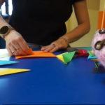 na zdjęciu ręce składające kartkę, origami