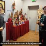 prowadzący wystawę, mężczyzna i kobieta na tle rzeźb Chrystusa