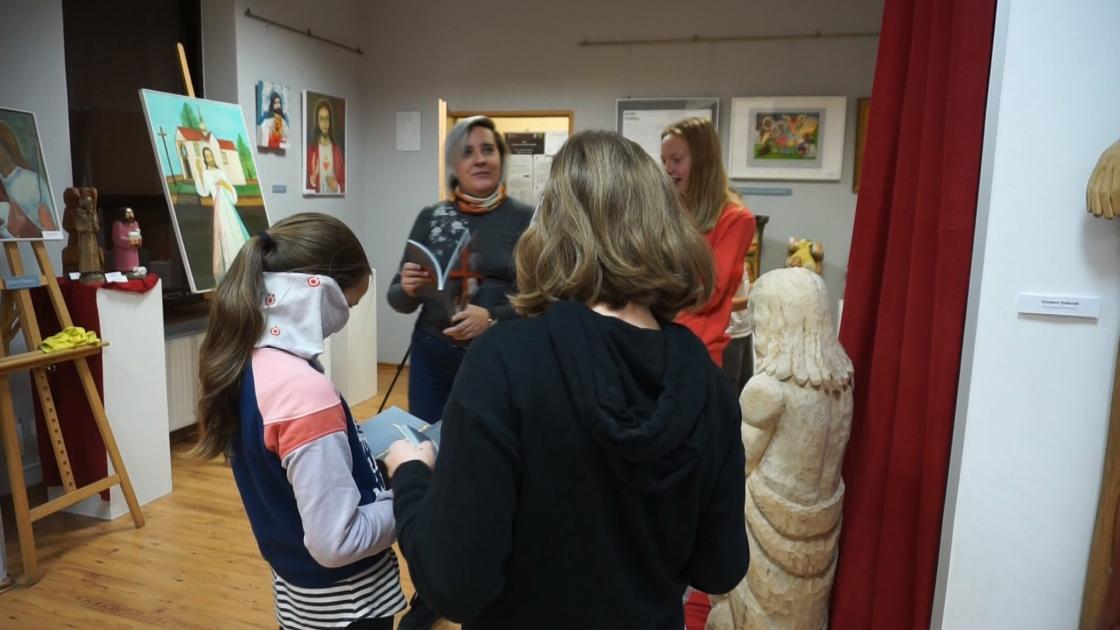 Uczestnicy wystawy na tle obrazów z wizerunkiem Chrystusa