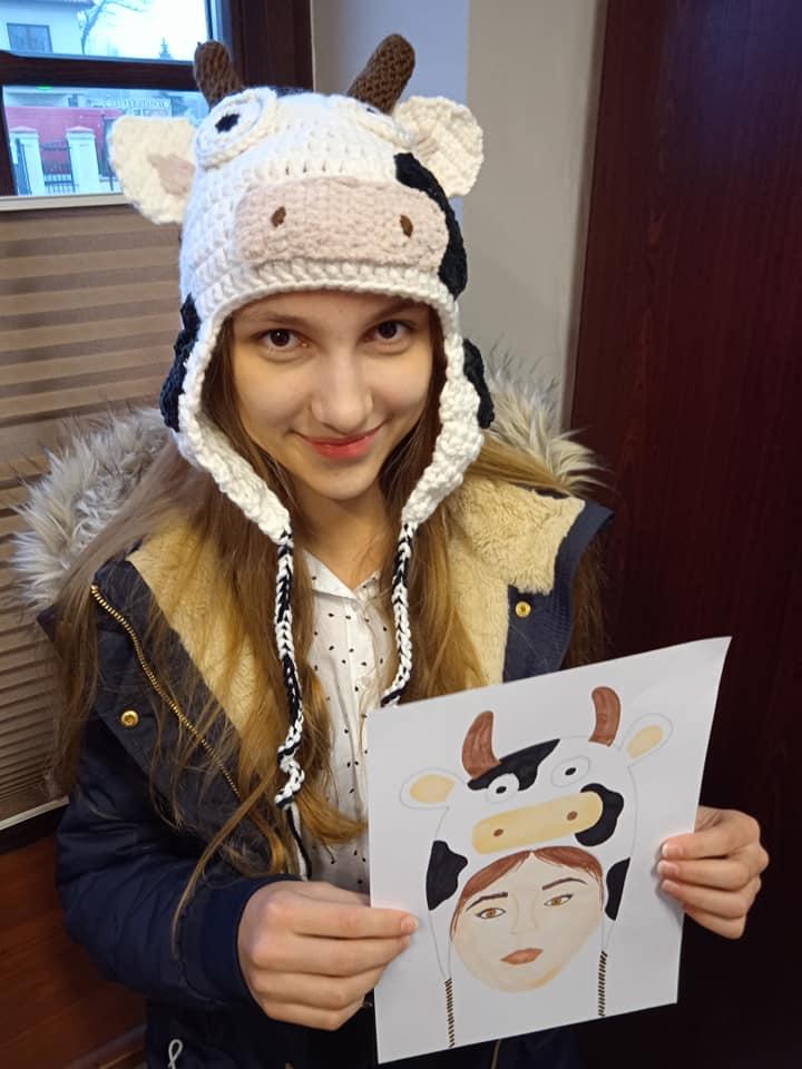 dziewczynka w czapce na głowie, czapka krowa, dziewczynka w dłoni trzyma obrazek przedstawiający czapkę krowę