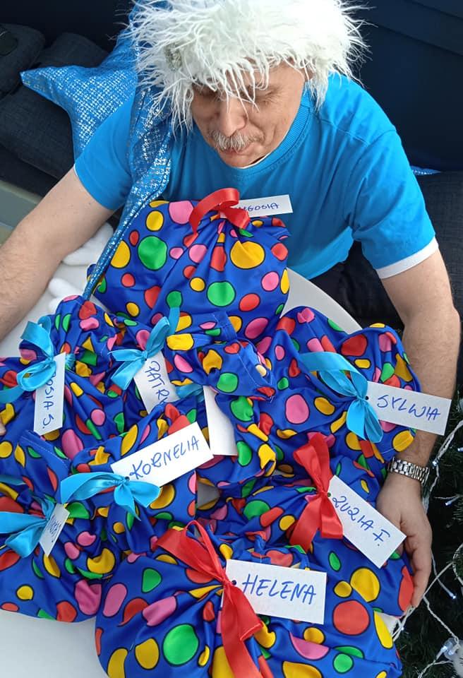 woreczki w groszki z prezentami, nad nimi mężczyzna w niebieskiej bluzce i czapce