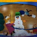 Zimowy obrazek ułożony z różnych materiałów, bałwanek, dziewczynka, piesek