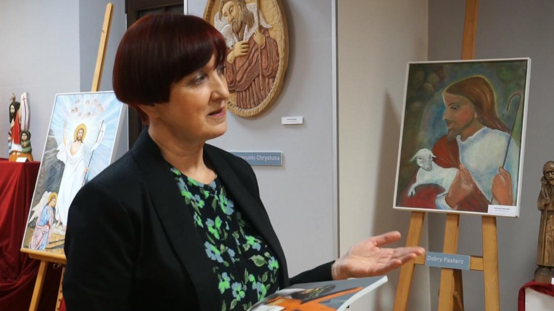 Danuta-Wachowska/Danuta Wachowska, kobieta prezentująca prace na wystawie w tle obrazy z Chrystusem