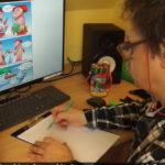 Krzysztof Dumka, mężczyzna rysujący komiks, w tle monitor komputera