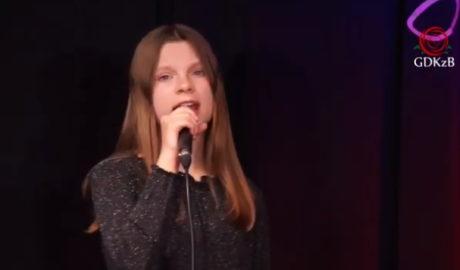 Młoda dziewczyna na scenie z mikrofonem w dłoni