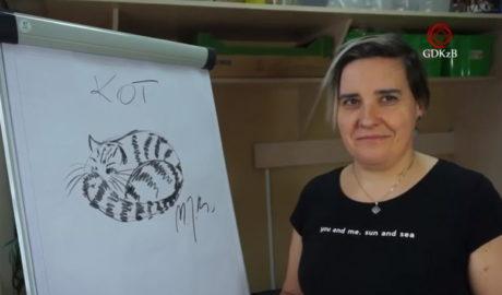 Kobieta przy sztaludze na której narysowany jest kot
