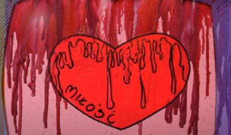 czerwone serce z napisem miłość narysowane na podkładce na której widać stopione kredki