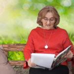 Kobieta w czerwonej bluzce, okularach. KObieta siedząca na ławce czytająca książkę