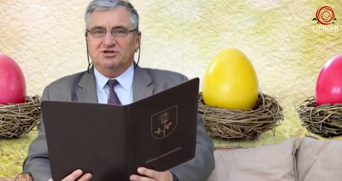 wójt gminy ksawerów Adam Topolsi, mężczyzna w garniturze czyta książkę. W tle zdjęcia kloorowe pisanki