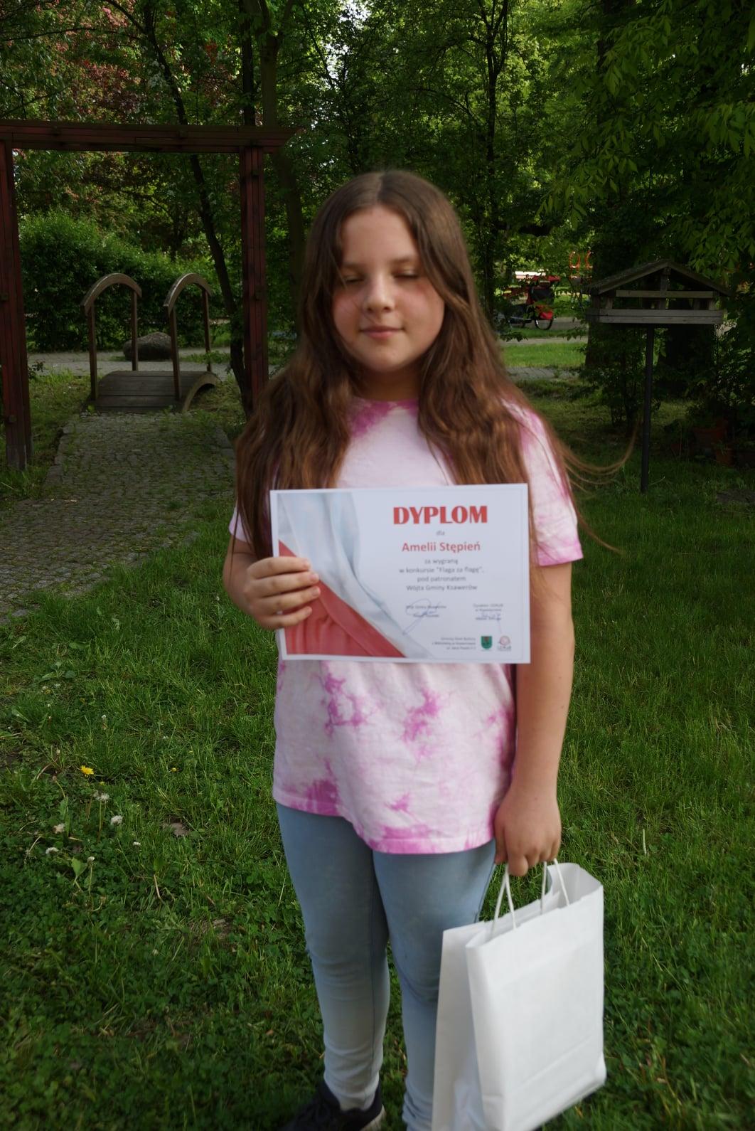 dziewczynka w długich włosach stojąca z papierową torebką i dyplomem w dłoni. W tle drzewa