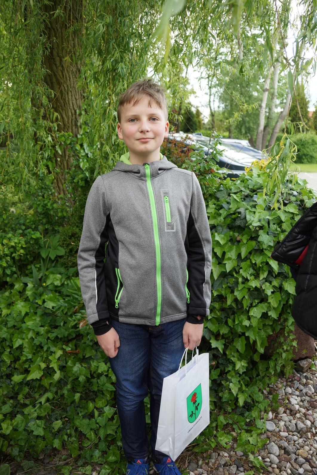 chłopiec w szarej bluzie z papierową torbą z logo gminy Ksawerów w tle drzewa