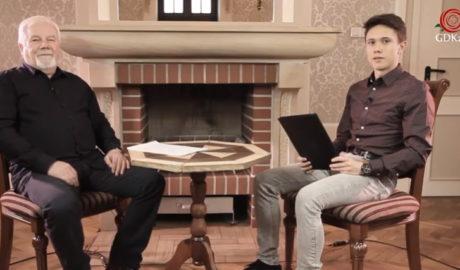 Dwóch mężczyzn siedzących przy kominku. Pomiędzy nimi okrągły stolik