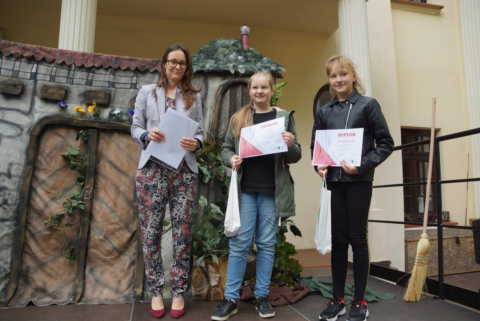 Zdjęcie przedstawia trzy osoby. Kobieta w spodniach w kwiaty wręcza dyplom, obok stoją dwie dziewczynki z dyplomami w dłoni