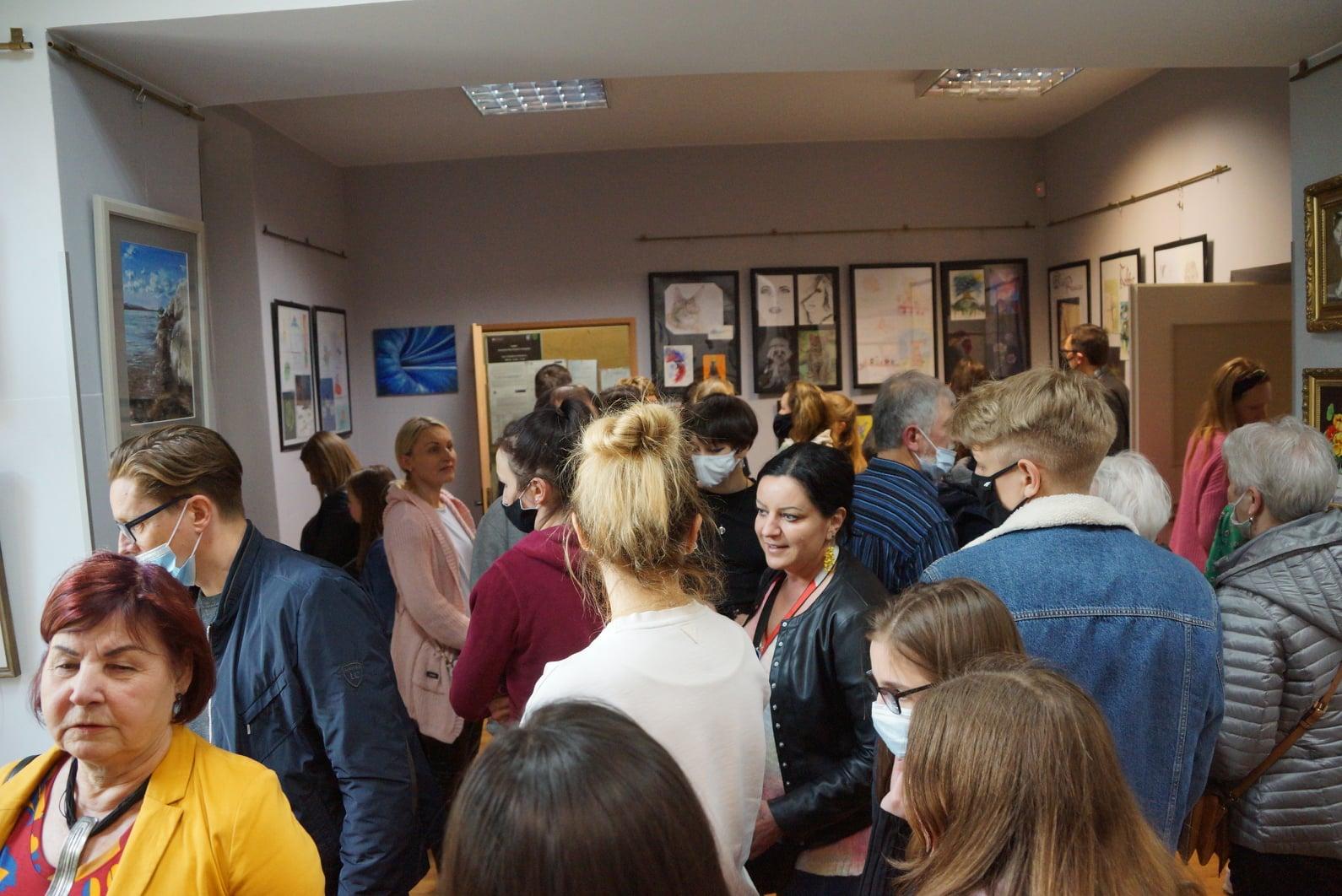 zdjęcie przedstawia osoby, zwiedzające galerię obrazów