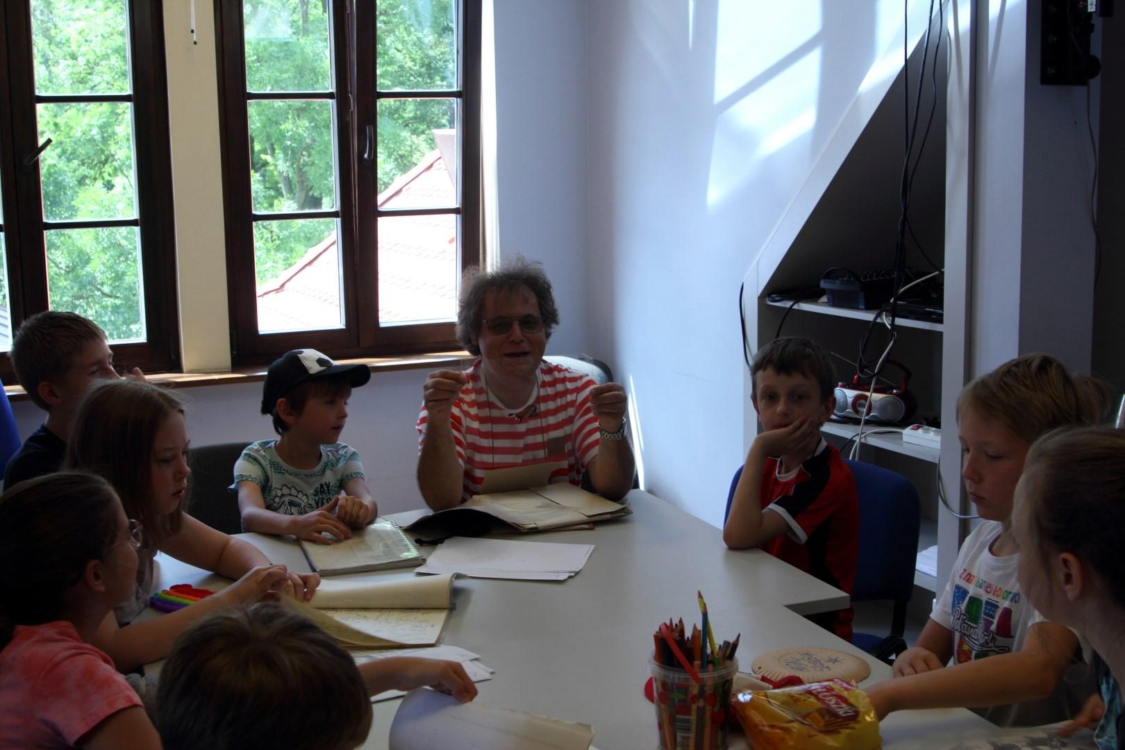 Na zdjęciu uczetnicy warsztatów (dzieci) siedzący przy stolikach. Pośród nich siedzi wychowawca pokazujący obrazki