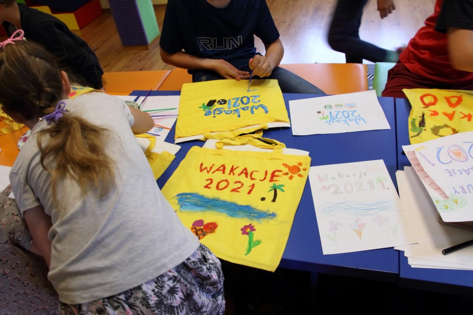 torby  w koloże żółtym leżące na stole. Dzieci wykonują na nich swoje rysunki, malując farbami