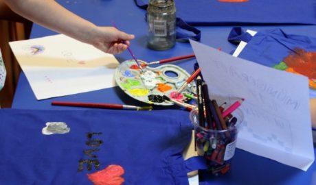 Na zdjęciu widoczne są granatowe torby leżące na stolikach. Dzieci malują farbami torebki dla najbliższych