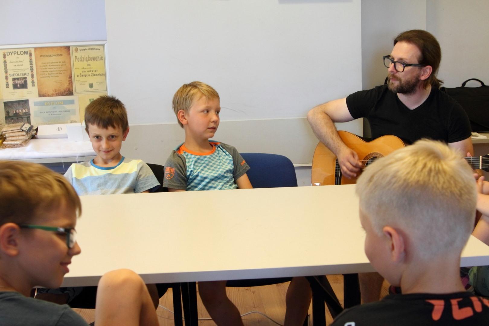 na zdjęciu czterech chłopców siedzących w sali przy stole słuchających jak mężczyzna gra na gitarze.