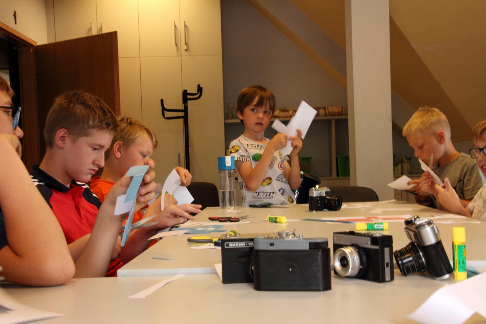 na zdjęciu dzieci stojące przy stolikach, sklejające model aparatu fotograficznego