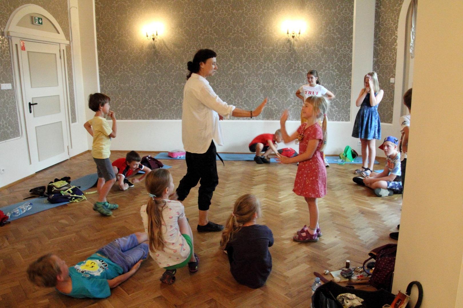 Dzieci będące na dużej sali. Część dzieci leży na karimatach, dwójka stoi wokół prowadzącej zajęcia kobiety