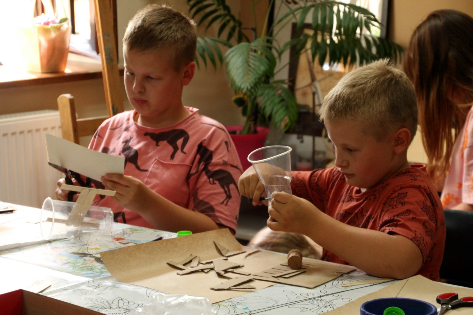 Na zdjęciu dwóch chłopców, którzy tworzą kosmiczny pojazd. Jeden z nich przecina szary kartonik, drugi trzyma nożyczki przy plastikowym kubeczku