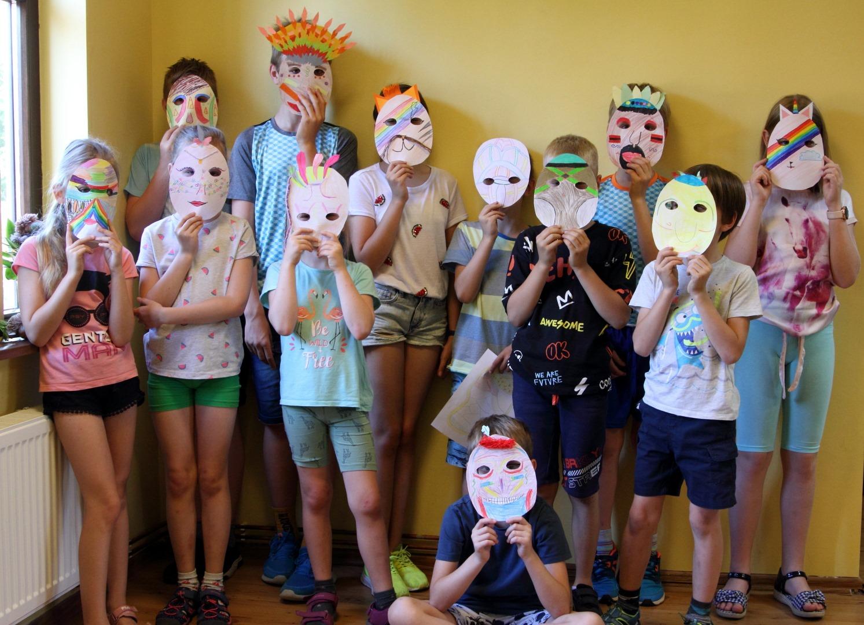 Grupa dzieci, chłopcy i dziewczynki trzymający wykonane przez siebie maski