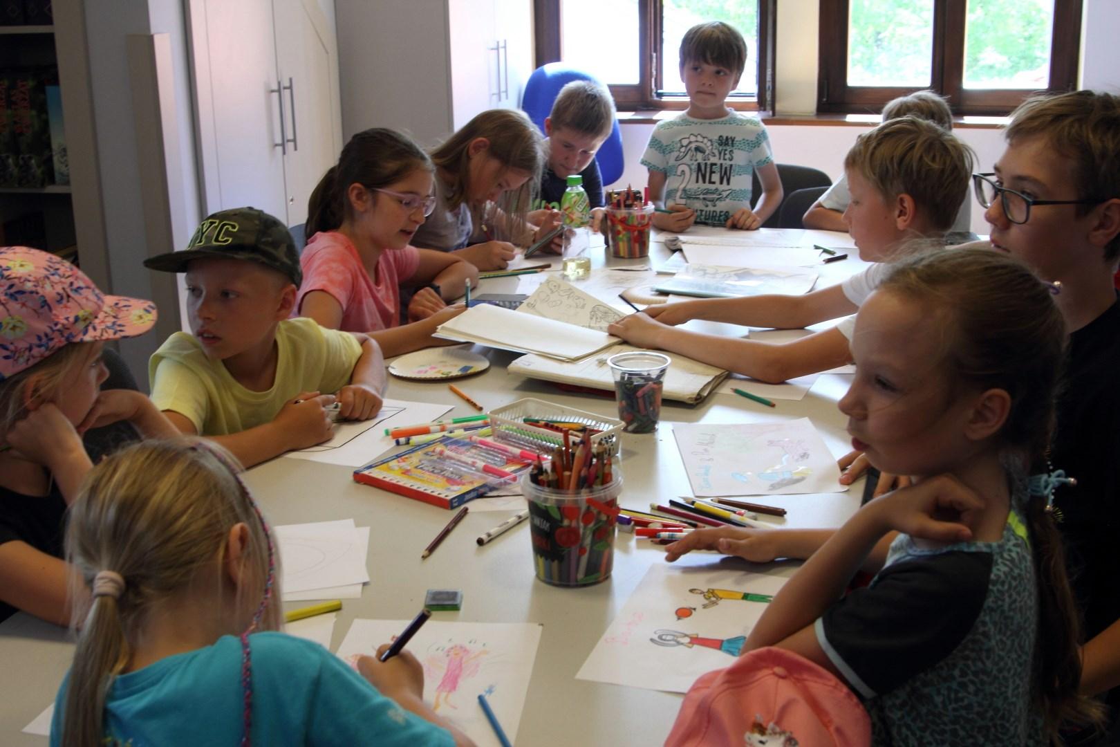 Dzieci w pracowni siedzące przy stoliku, przed nimi kartki i pisaki rozrzucone po stole. część dzieci siedzi , pozostałe rysują
