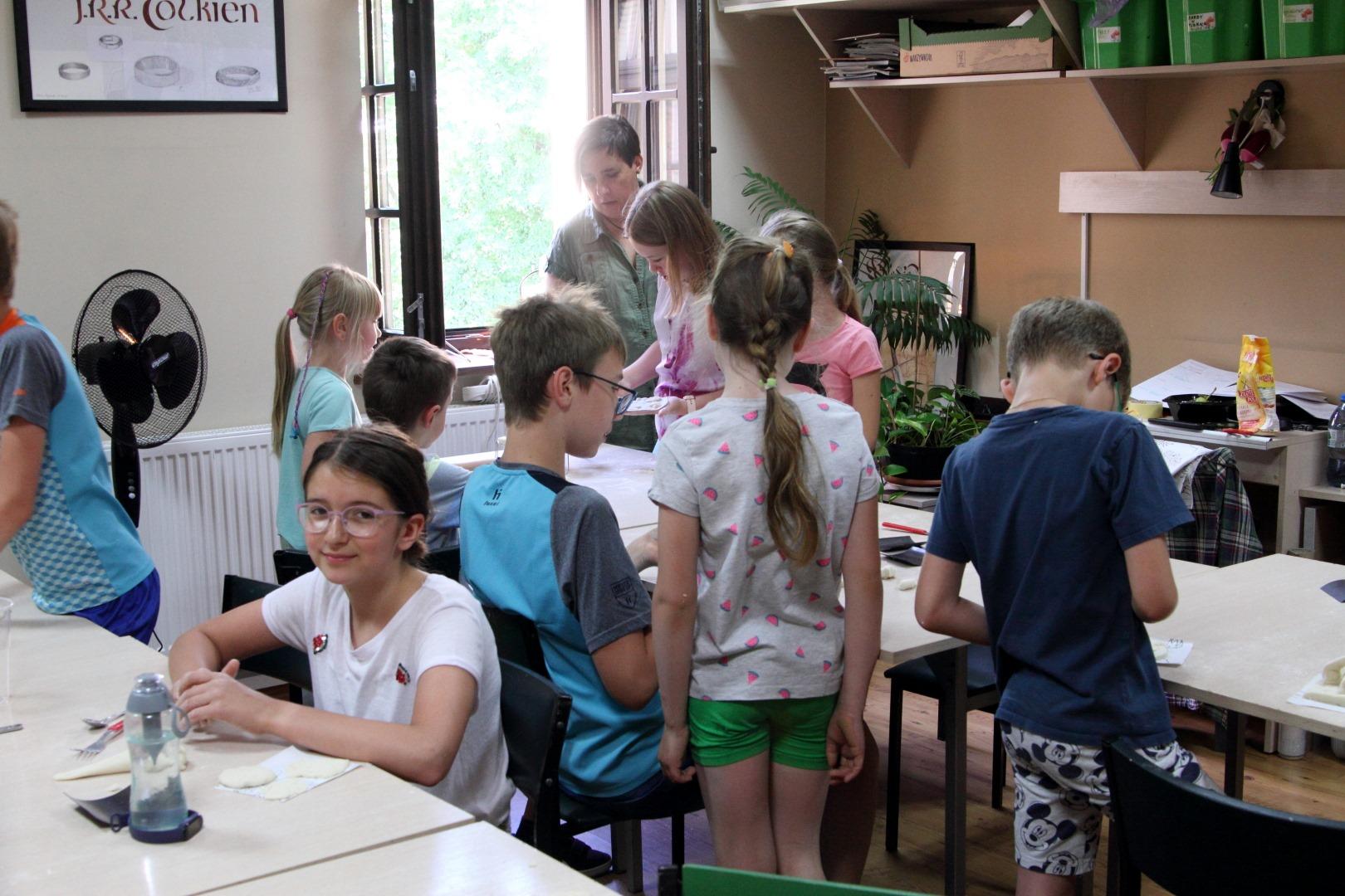 Grupa dzieci w pracowni plastycznej siedzące przy stolikach