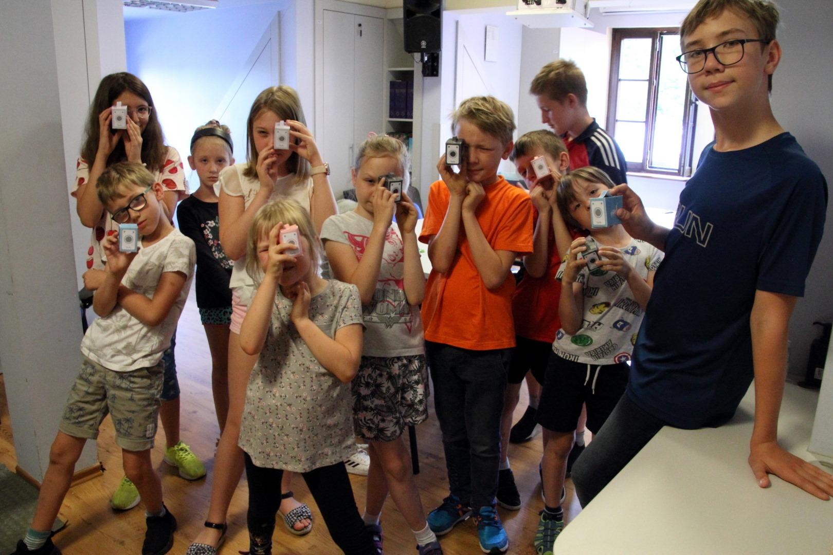 na zdjęciu grupa dzieci trzymająca zrobione z kartony aparaty fotograficzne