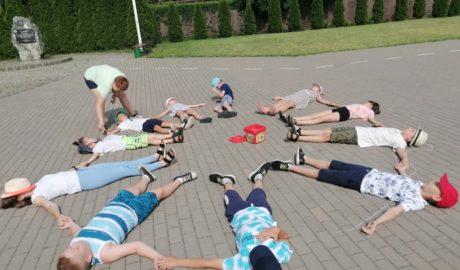 dzieci leżące na kostce przed budynkiem, ułożone w krąg, odrysowywanie konturów dzieci