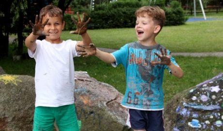 na zdjęciu dwóch chłopców, którzy mają pomalowane dłonie farbą