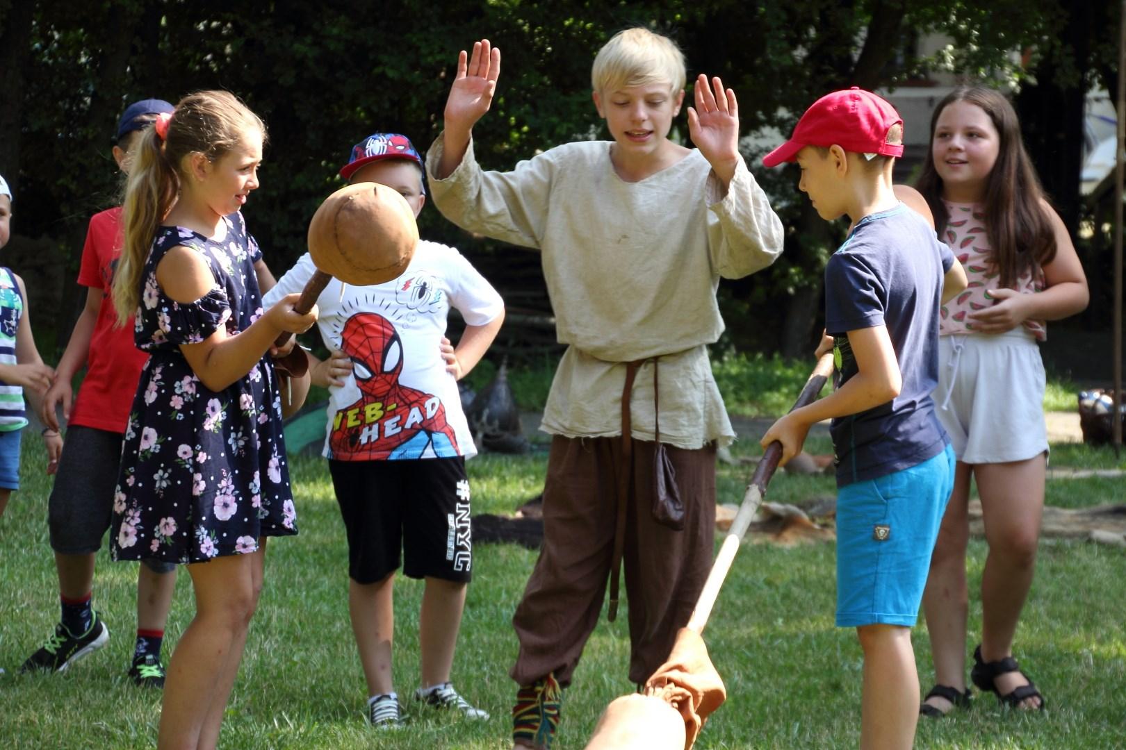 siedmioro dzieci bawiących się na trawie