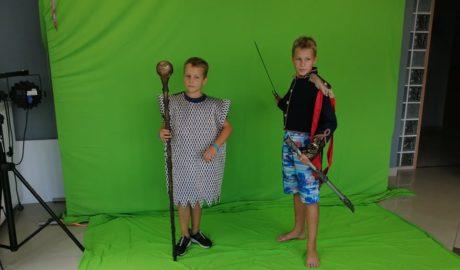 dwaj chłopcy stojący na zielonym tle, w strojach rycerzy