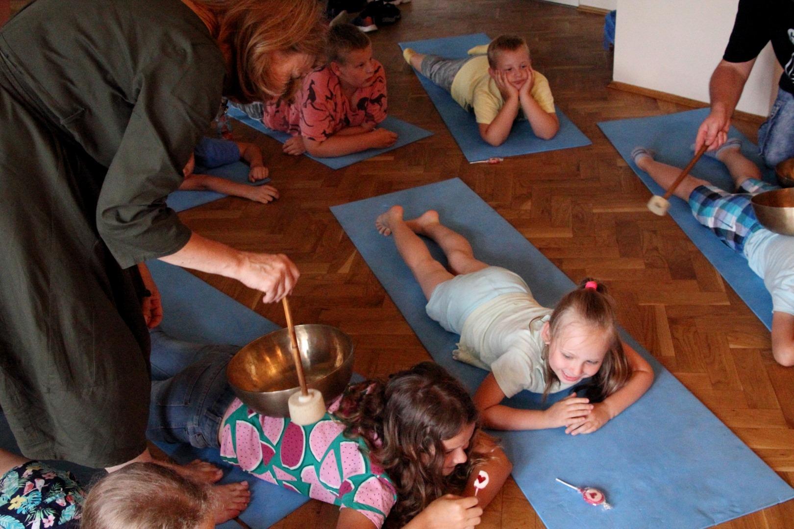 dzieci leżą na karimatach, nad dziewczynką pochyla się kobieta trzymająca w ręku pałeczkę z gąbki
