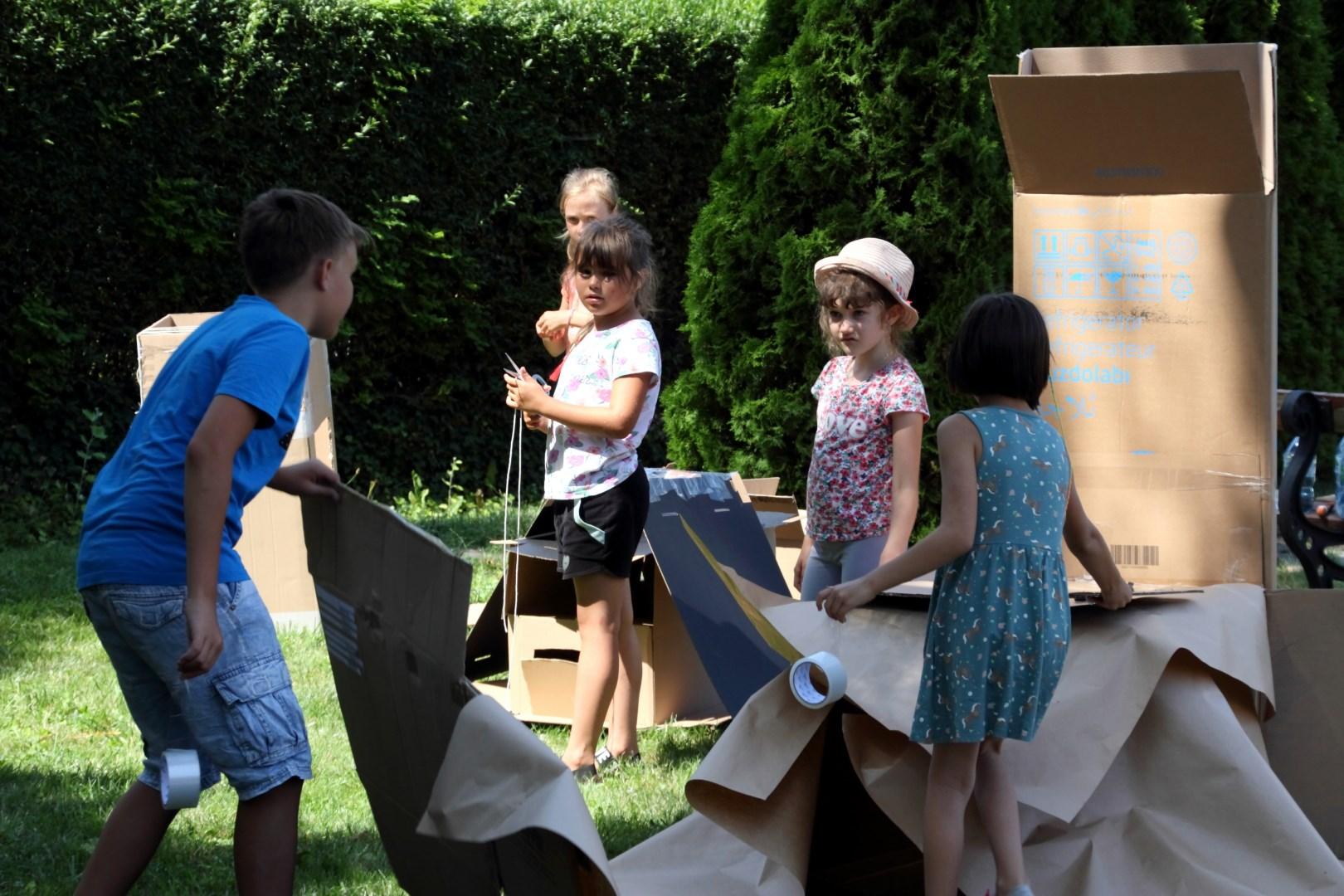 Na zdjęciu piątka dzieci, bawiąca się na trawie. Dzieci stoją przy kartonowych pudełkach tworząc budowle