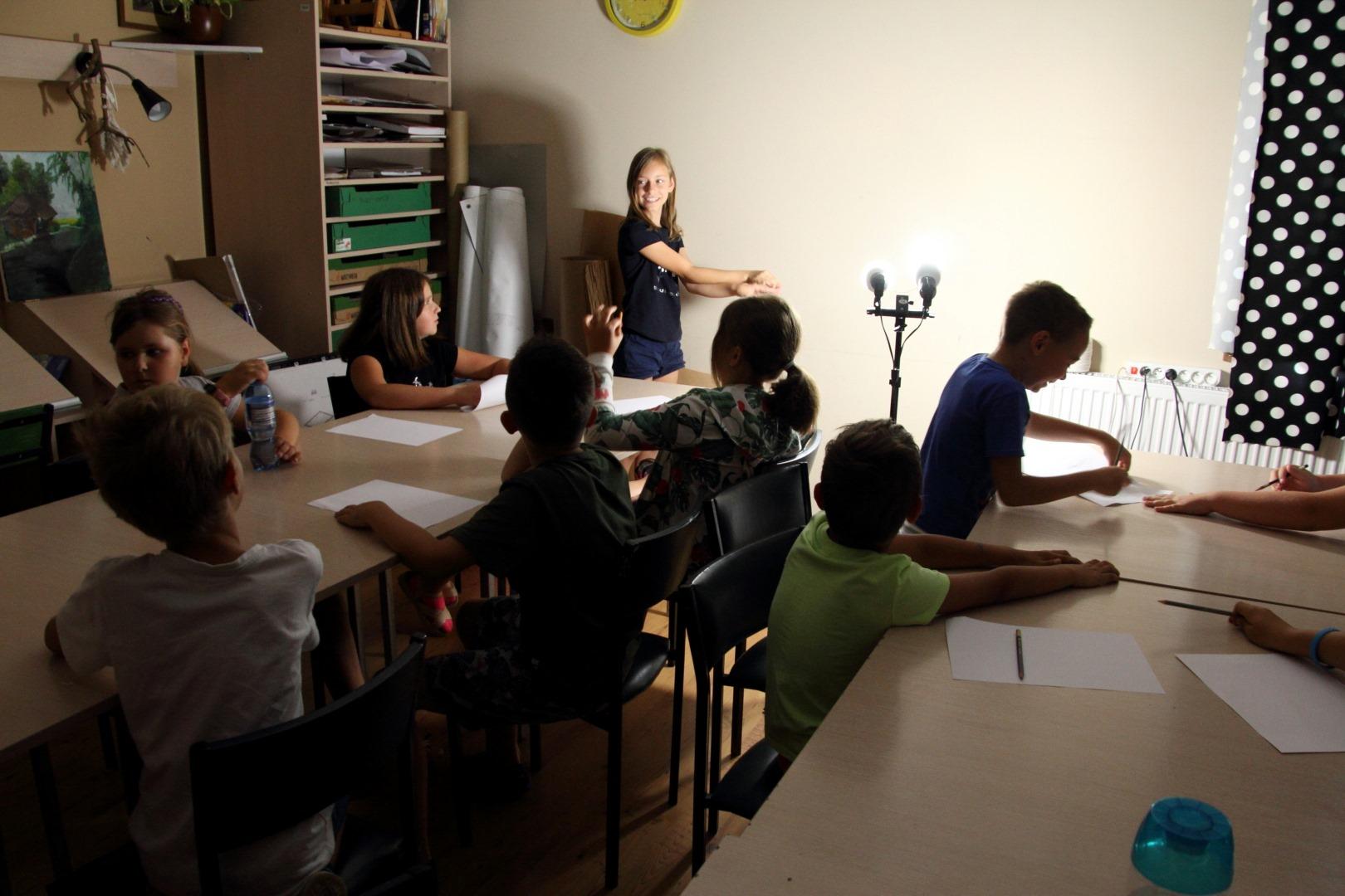 grupa dzieci siedząca w zacienionym pomieszczeniu, dziewczynka stoi uśmiechnięta przy ścianie i rękoma rzuca cień na ścianę - tworząc teatr cieni.