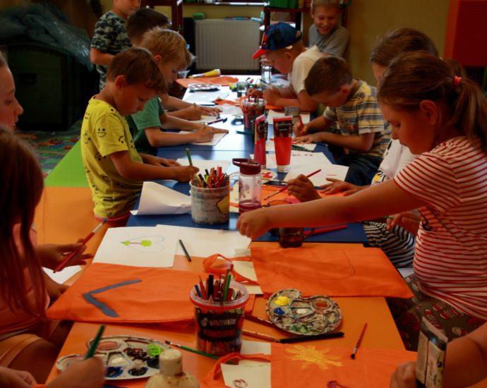 Na zdjęciu grupa dzieci , chłopcy i dziewczynki siedzący przy stole. Przed nimi leżą kredki, palety w z farbami oraz tuby farb. Dzieci malują wzory na pomarańczowych torbach