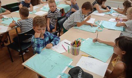 Dzieci siedzące przy stolikach, malujace farbam na płucennych torbach koloru niebieskiego