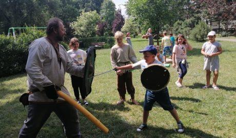 na zdjęciu grupa dzieci oraz mężczyzna w słowiańskim stroju. Na pierwszym planie chłopiec trzymający tarczę i miecz
