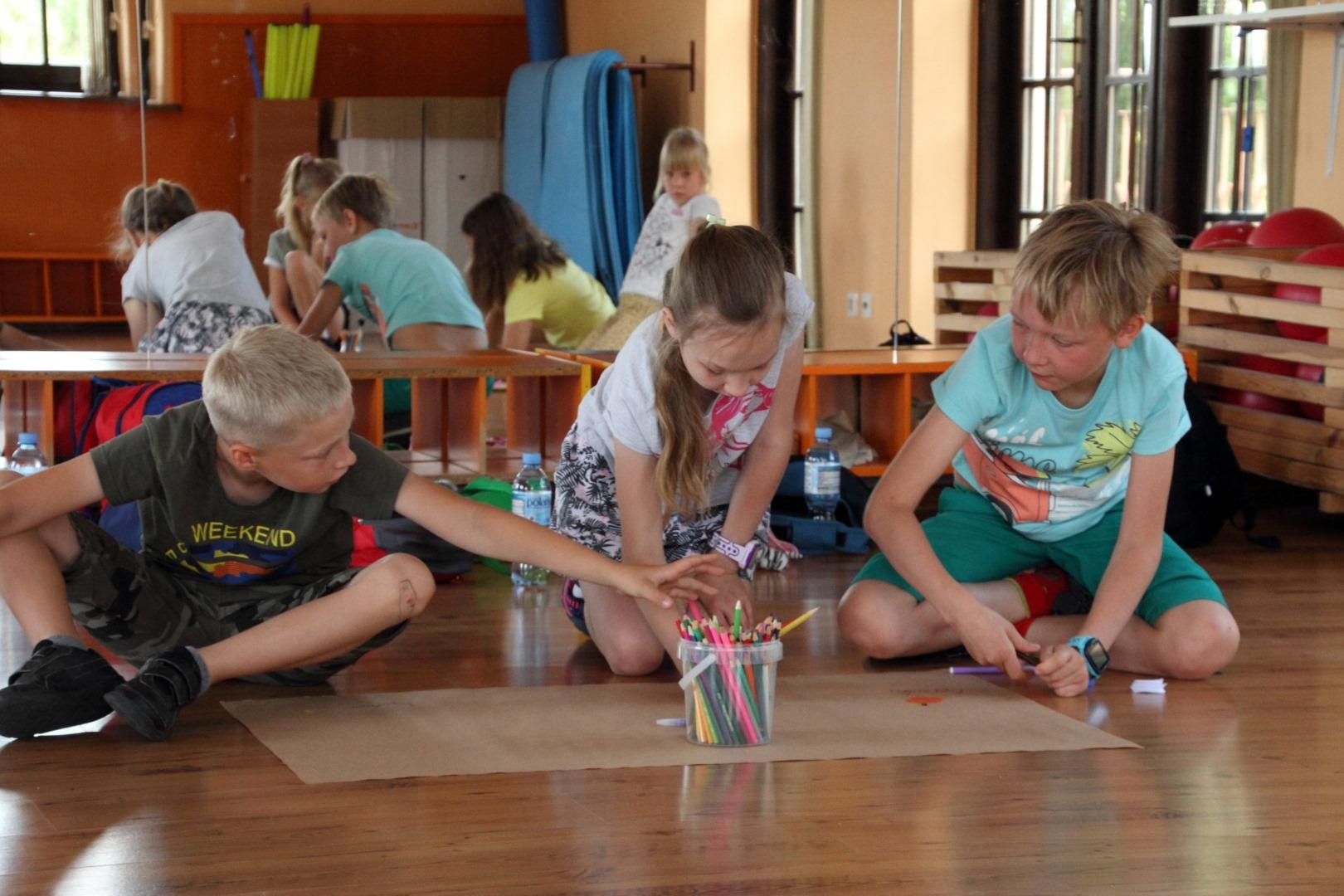 Na zdjęciu czworo dzieci siedzących na podłodze. Dzieci malują na papierze pakowym. Za dzieśmi lustra