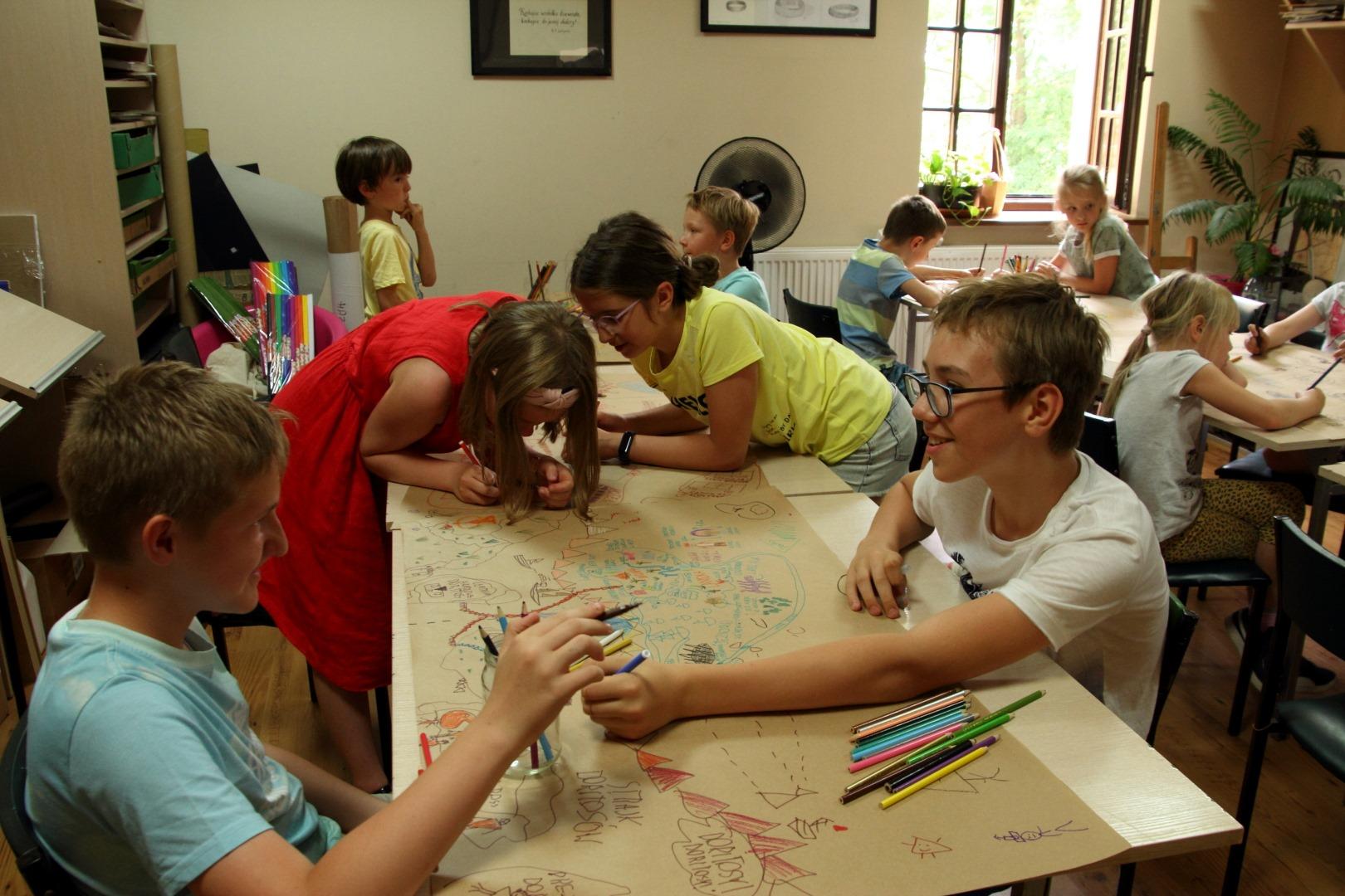 Na zdjęciu widać dzieci siedzące przy stolikach. Dzieci tworzą mapę