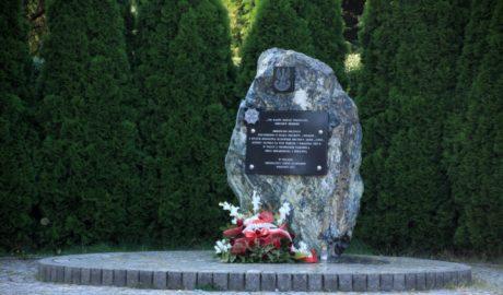 Zdjęcie przedstawia obelisk (kamień) przed którym znajduje się wieniec biało czerwonych kwiatów