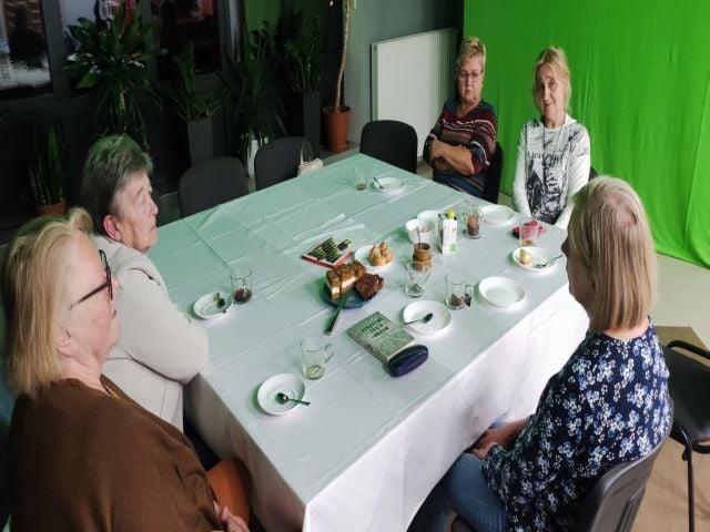 na zdjęciu pięć kobiet siedzących przy stole, nakrytym białym obrusem. Na stole talerze, szklanki oraz ciasto.